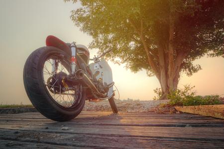 motobike: Honda C70 custom back view with paddy field view background