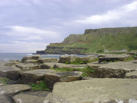 northern ireland: A scenic view of the Giants Causeway in Northern Ireland and the cliffs in the distance Stock Photo