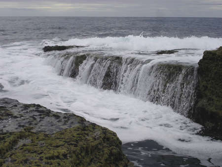 northern ireland: Water crashes over the basalt rocks of the Giants Causeway in Northern Ireland on a stormy day
