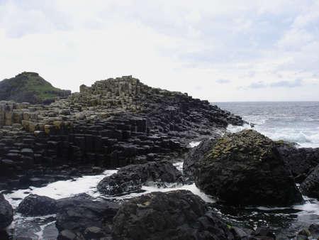 北アイルランドでのジャイアンツコーズウェイの玄武岩の岩に対する水がクラッシュします。 写真素材