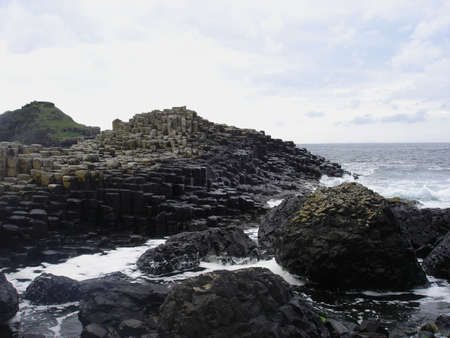 northern ireland: Water crashes against the basalt rocks of the Giants Causeway in Northern Ireland Stock Photo