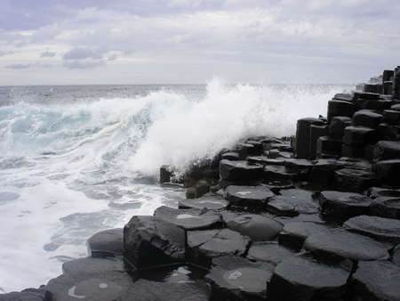 northern ireland: A violent ocean crashes against the basalt rocks of the Giants Causeway in Northern Ireland on a turbulent day Stock Photo
