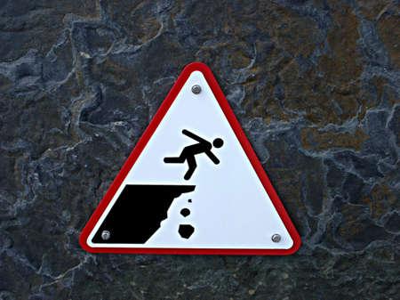 Bordje waarschuwing van de rand van een klif en vallend gesteente Stockfoto