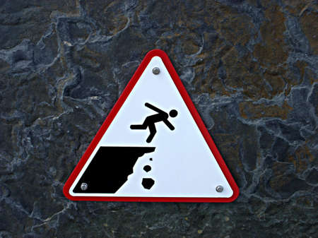 alarming: Peque�a se�al de advertencia del borde de un acantilado y la ca�da de rocas Foto de archivo