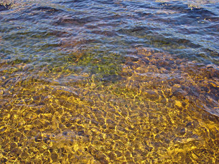Rippled water with yellow stones beneath makes for an interesting background Imagens