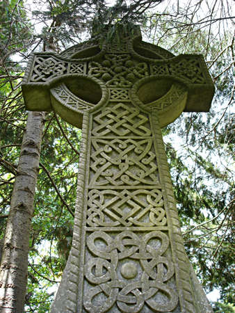 An old stone celtic cross, green with moss, rises up into its wooded surroundings