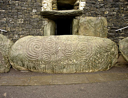An ancient, massive boulder inscribed with early celtic spiral drawings in front of the main entrance at Newgrange in Ireland