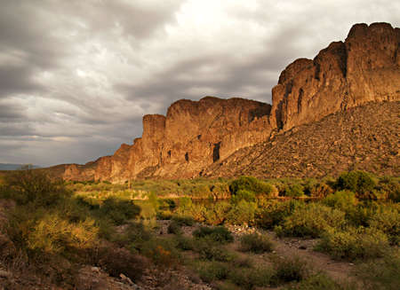 Arizona desert cliffsides highlighted by the dying sun with a storm brewing in the distance Stock Photo - 3196175