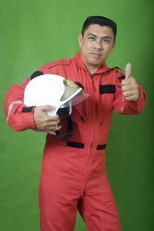 Rescue firefighter holding safety helmet and thumb up isolated on green photo