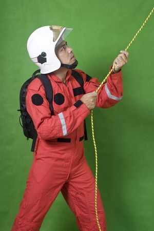 Rescue firefighter pulling a rope isolated on green photo