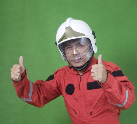 Rescue firefighter wearing safety helmet while thumbs up isolated on green photo