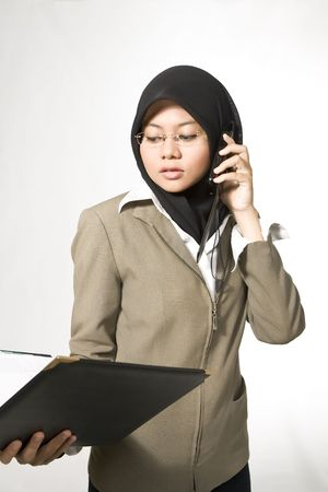 Muslim young businesswomen make a phone call while holding a book