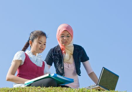 two girls studying together in the field photo
