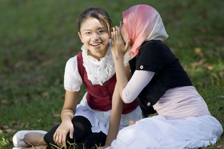 Two muslim girl whispers each other photo