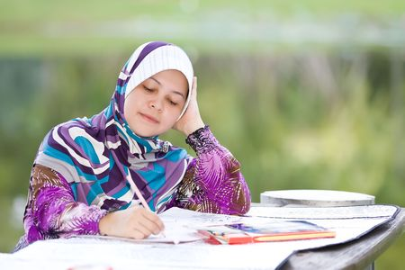 A female teacher is checking the work of school students
