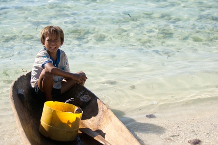 SIBUAN ISLAND, MALAYSIA - JANUARY 8 : A Sea Gypsies boy was in small boat after came back from catch the fish on January 8, 2011 in Sibuan Island, Sabah, Malaysia.