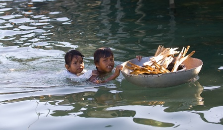 SEMPORNA, MALAYSIA - January 7: Children Sea Gypsies use a large pot as the main transport for carrying goods to their daily needs on January 7, 2011 in Semporna, Sabah, Malaysia.
