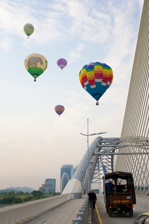PUTRAJAYA, MALAYSIA - MARCH 18 : Hot air balloons crossing the bridge at the 3rd Putrajaya International Hot Air Balloon Fiesta March 18, 2011 in Putrajaya, Malaysia. Editorial