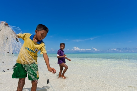 SABAH, MALAYSIA - JAN 8 : Children of the Sea Gypsies was catch a fish at the beach on January 8, 2011 in Mantabuan Island, Sabah, Malaysia. Most beautiful island in Sabah. Stock Photo - 9158246