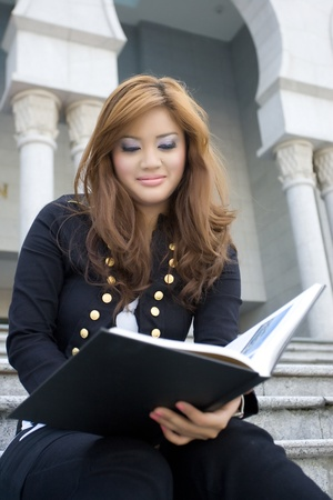 Young beautiful woman reading a book photo