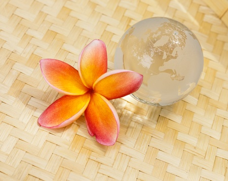 Yellow plumeria and crystal globe on bamboo mat photo
