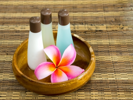 Plumeria and shampoo bottles in wooden bowl photo