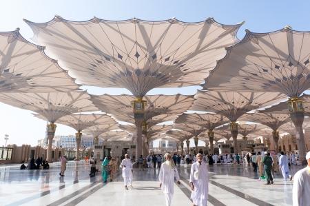 ksa: MEDINA, KINGDOM OF SAUDI ARABIA - SEP 26   Pilgrims walk outside Masjid Nabawi after morning prayer Sep 26, 2013 in Medina, KSA  Thousand of muslims comes from all around the world
