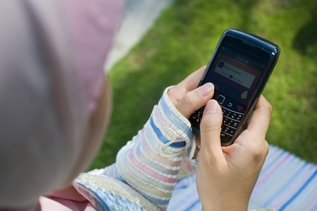 A girl playing with handphone Stock Photo