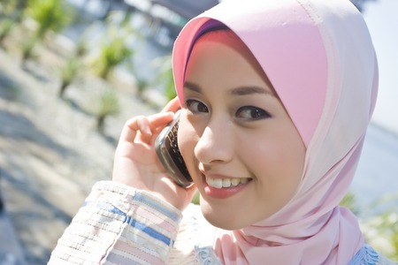 purdah: a young girl wearing scaft is making phone calls