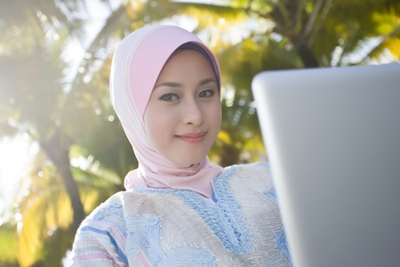veiled: a young girl wearing scaft are using laptop