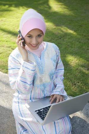 make a call: Muslim beautiful girl make a phone call while holding notebook