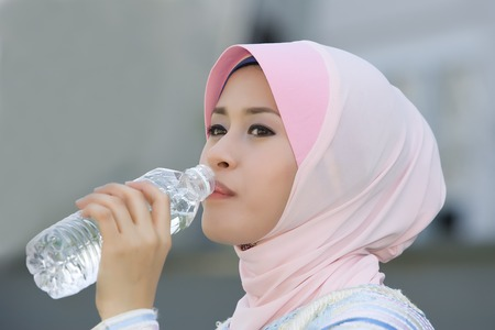 purdah: A young girl drinking mineral water