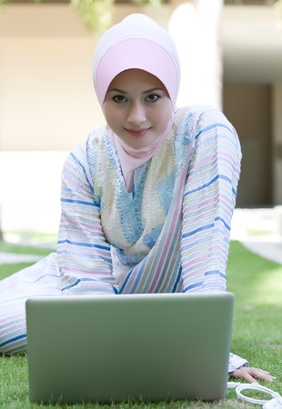 purdah: Portrait of at he muslim girl play with laptop