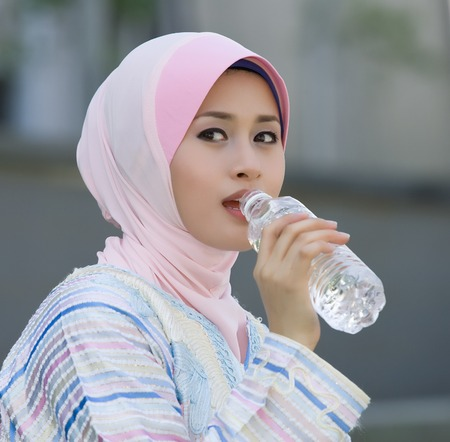 purdah: beautiful muslim women are drinking water Stock Photo