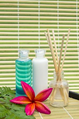 rattan mat: Shampoo bottles, fragrance and red plumeria on rattan mat Stock Photo