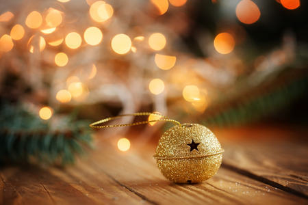 jingle bell: Gold Metal Jingle Bell with star on Wooden Table. Christmas background