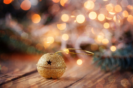 Gold Metal Jingle Bell with star on Wooden Table with boke and glitter sparks.