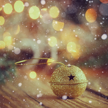 jingle bell: Metal Jingle Bell with star on Wooden Table with snow. Christmas background Stock Photo