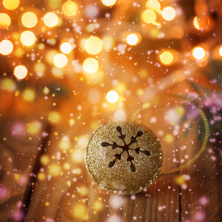jingle bell: Gold Metal Jingle Bell with snowflake on Wooden Table with boke and glitter sparks. Christmas background. Stock Photo
