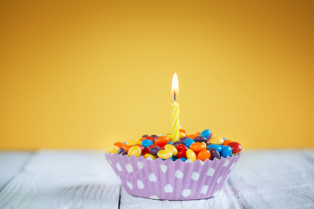 holiday party: Decorated Birthday cupcake with one lit candle and colorful candies on yellow background