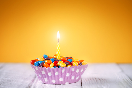 Decorated Birthday cupcake with one lit candle and colorful candies on yellow background