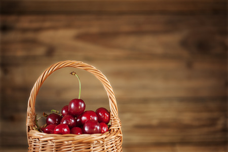 basket: Ripe Sweet Cherries in  Basket closeup on Rustic Wooden background