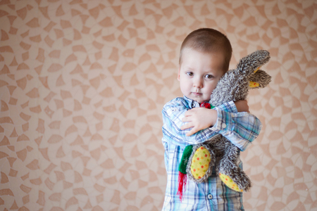 2 persons only: Little boy is holding his teddy  rabbit.