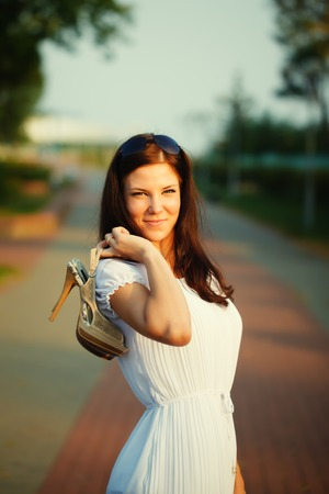 high heeled shoes: Brunette beautiful woman holding a high heeled shoes Stock Photo