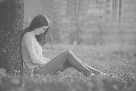 enchantress: The lonely girl sits at a tree, outdoors. The photo in old black-and-white style