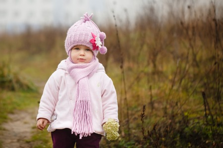 warm clothing: Happy baby girl in a pink hat and scarf laughs in autumn