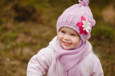 pink hat: Happy baby girl in a pink hat and scarf laughs