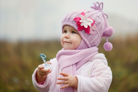 blows: A little baby blows bubbles in autumn