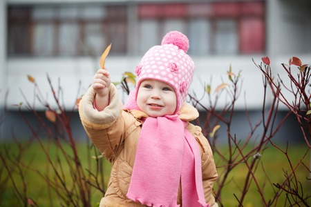 pink hat: Smiling baby girl in a pink hat and scarf laughs in autumn park. Stock Photo