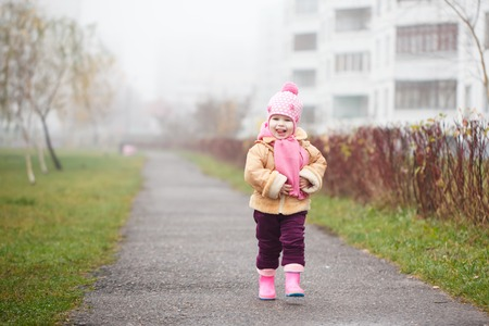The happy girl in a pink hat and a scarf and rubber boots laughs. Standard-Bild